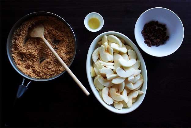 Prepare the filling: Buttered breadcrumbs mixed with sugar and cinnamon, melted butter, sliced apples, soaked raisins.