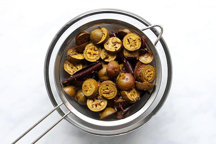 Strained cut green walnuts for spiced walnut liqueur recipe