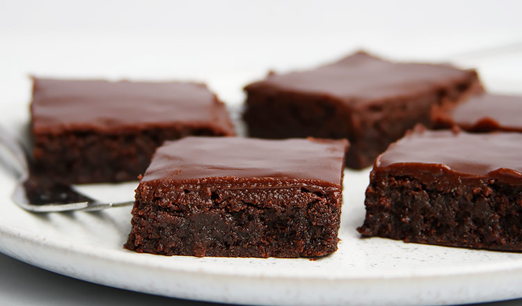 Poppy seed brownies with ganache on plate